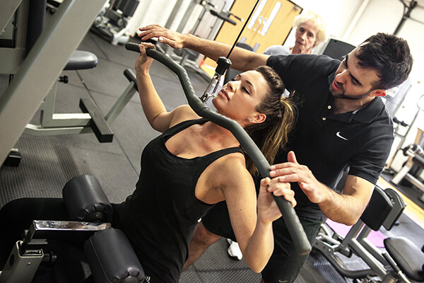 a woman being coached on a lateral pull down machine