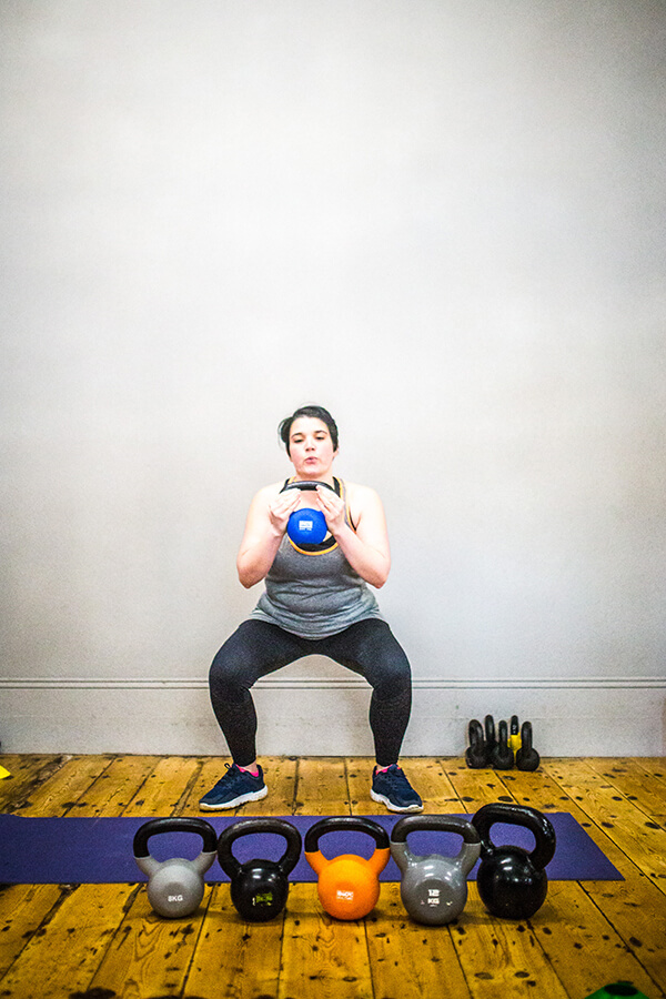 woman doing a kettle bell squat with row of kettlebells in front of her