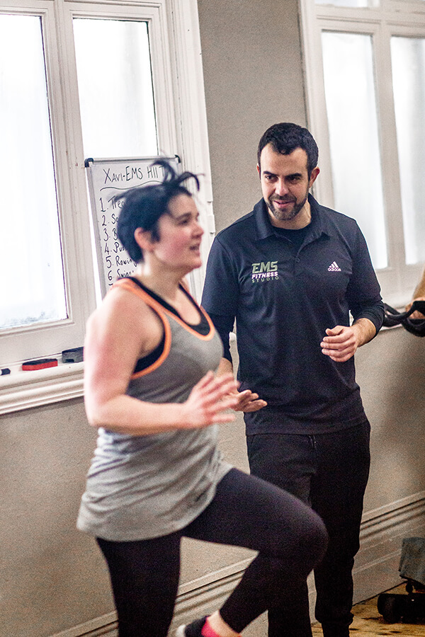 a trainer at ems fitness working with a client